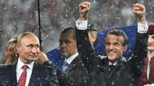 بوتين يحدق في الرئيس الفرنسي إيمانويل ماكرون الذي كان يحتفي بفوز منتخب بلاده في كأس العالم الأحد 15 تموز/يوليو 2018.
