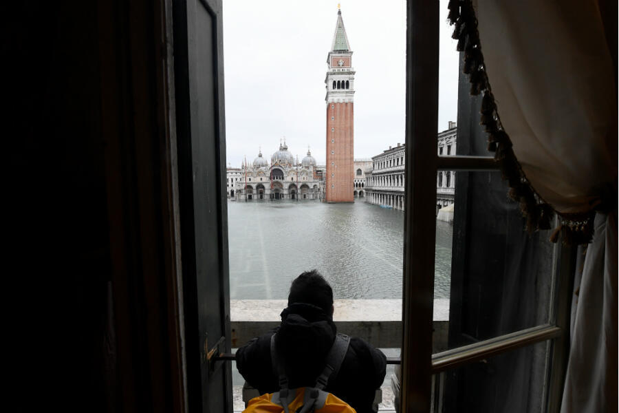 A man observes the flooded St. Mark's Square as high tide reaches its peak in Venice, Italy, on November 15, 2019.