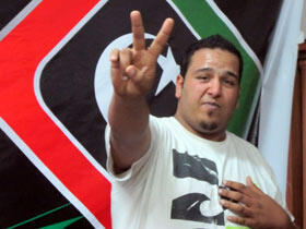"Mutaz el Obidy flashes the ubiquitous Libyan pro-democracy ""V"" for victory sign. Photo: Leela Jacinto"