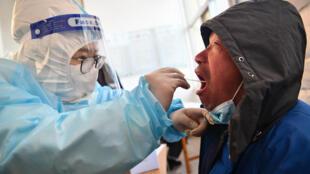عامل صحة يجري فحص كورونا لرجل في شيجياتشوانغ، في 6 كانون الثاني/يناير 2021