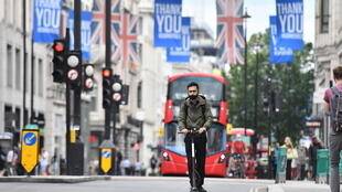 Un hombre con mascarilla circula en monopatín por Oxford Street, en Londres, el 14 de julio de 2020