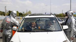 أعضاء في الهلال الأحمر الإيراني يفحصون درجة حرارة راكبي سيارات في مخرج الطريق السريع في طهران، 26 آذار/مارس 2020.