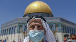 رجل مسلم يقف أمام مسجد قبة الصخرة في الحرم القدسي في القدس الشرقية المحتلة بعد صلاة الجمعة 21 آب/أغسطس 2020 ويضع كمامة واقية من فيروس كورونا المتسجد
