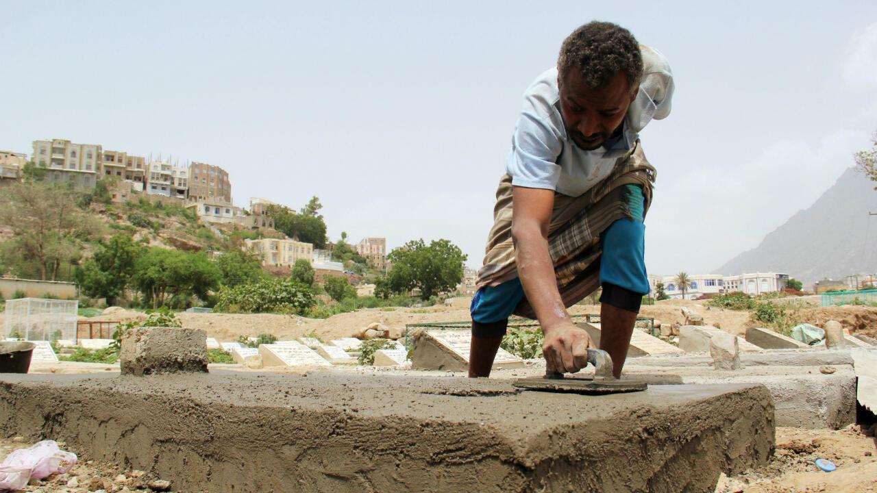 Un trabajador construye una lápida en un cementerio donde se ha enterrado a víctimas del nuevo coronavirus. Taiz, Yemen, el 25 de junio de 2020.