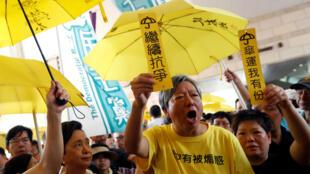 Simpatizantes del movimiento de los 'Paraguas Amarillos' sostienen sombrillas amarillas y un cartel para apoyar a los líderes del movimiento fuera de la corte en Hong Kong, China, el 24 de abril de 2019.