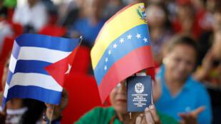 Un simpatizante del presidente Nicolás Maduro, con una copia de la constitución venezolana y las banderas de Venezuela y Cuba, participa en una reunión en apoyo de su Gobierno. Palacio de Miraflores en Caracas, Venezuela, el 26 de enero de 2019.