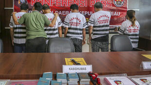 Suspects (in white striped shirts), allegedly linked to the death of an Indonesian sailor aboard a Chinese fishing vessel face a wall when presented to the media during a police press conference in Batam
