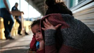 Una niña hondureña y su madre huyen de la pobreza y la violencia en su país de origen, esperan en el paso fronterizo después de que se les negó la entrada a Estados Unidos el 25 de junio de 2018 en Brownsville, Texas.