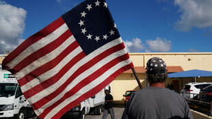 Un manifestante con una bandera grita a otro hombre que sale de las oficinas electorales en el condado de Broward, Florida, el 12 de noviembre de 2018.