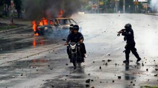 Un policía antidisturbios dispara su escopeta contra dos hombres durante una protesta contra el gobierno del presidente de Nicaragua Daniel Ortega en Managua, Nicaragua 28 de mayo de 2018.