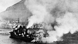 Le contre-torpilleur Mogador en feu, sa plage arrière détruite par un coup au but ayant fait exploser ses grenades anti-sous-marines, lors de l'attaque de Mers el-Kébir.