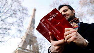 Gwendal Poullennec, International Director of Michelin Guides poses holding a copy of the Michelin Guide 2021 before the ceremony to award stars to French restaurants, in Paris, France, on January 18, 2021.