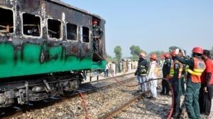 Un grupo de bomberos y rescatistas ante el tren que se incendió tras la explosión de una bombona de gas en su interior en cercanías a la ciudad de Rahim Yar Khan, en Pakistán, el 31 de octubre de 2019.