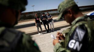 Miembros de la Guardia Nacional de México detienen a migrantes cubanos cuando intentaban cruzar ilegalmente la frontera entre Estados Unidos y México, en Ciudad Juárez, México, el 21 de junio de 2019.
