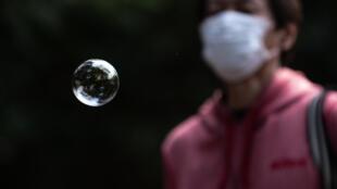 Una pompa de jabón flota suspendida en el aire frente a una persona con mascarilla en el parque japonés de Inokashira, el 19 de abril de 2020 en Tokio
