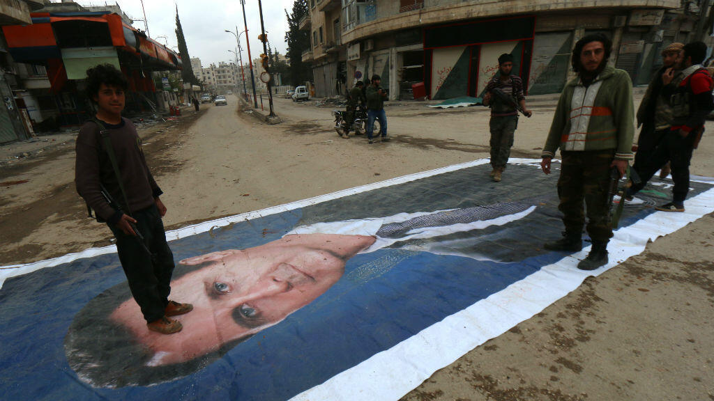 Islamist fighters stand on a portrait of Syrian President Bashar al-Assad in Idlib on March 29.