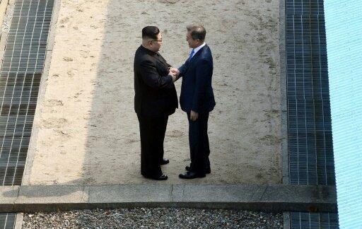 مصافحة بين الرئيس الكوري الجنوبي مون جاي إن ونظيره الشمالي كيم جونغ أون عند خط ترسيم الحدود بين الكوريتين في السابع والعشرين من نيسان/أبريل 2018