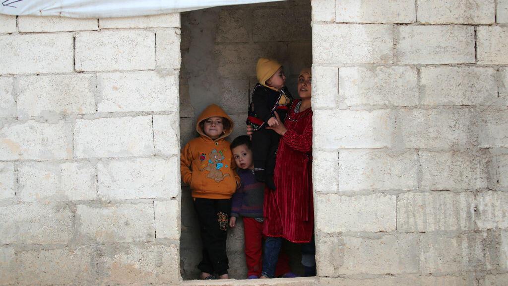 Los niños sirios desplazados internos miran desde su refugio un campamento en las afueras de Azaz