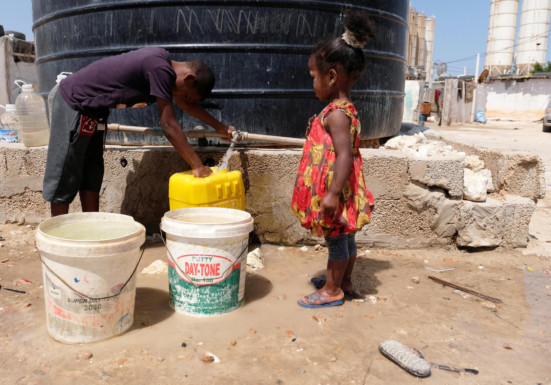 Des enfants libyens qui ont fui la ville de Tawergha remplissent des conteneurs d'eau dans un camp de déplacés à Benghazi, en Libye, le 19 juin 2019
