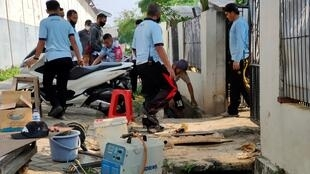 Officers checking the culvert used by a Chinese death-row prisoner to escape in Tangerang
