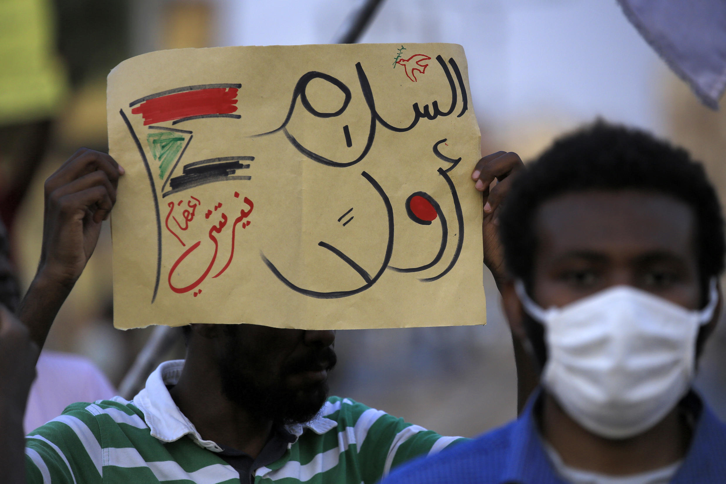 """File photo taken July 4, 2020, of a demonstrator holding up a sign reading in Arabic """"peace first"""" during a protest in Khartoum, Sudan."""