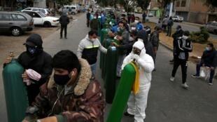 Decenas de personas esperan en una fila a poder recargar sus tanques de oxigeno en medio de la pandemia de coronavirus. En Lima, Perú, el 25 de junio de 2020.