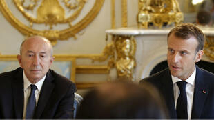 Michel Euler, AFP | French President Emmanuel Macron (R) sits next to Interior Minister Gérard Collomb as he leads a cabinet meeting on August 3, 2018, at the Élysée Palace in Paris.