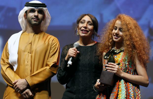 La réalisatrice Haifaa al-Mansour (centre), aux côtés de Cheikh Mansour, fils de l'émir de Dubaï Cheikh Mohammed ben Rachid al-Maktoum (gauche) et de la jeune actrice Waad Mohammed (droite), au festival de cinéma de Dubaï.