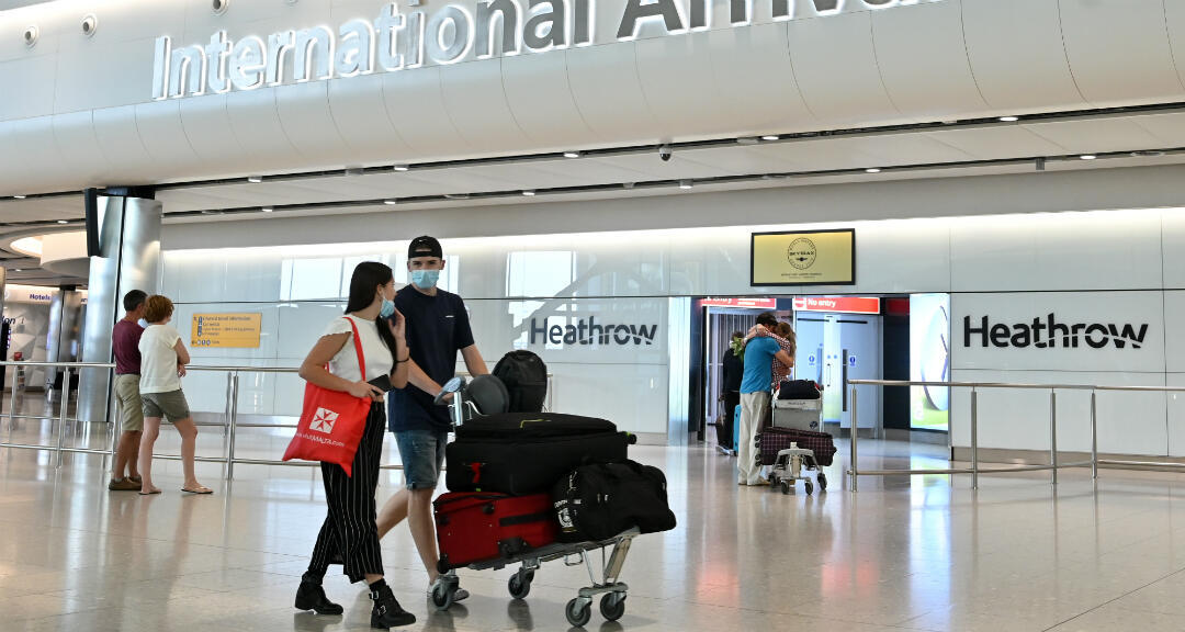 Pasajeros con mascarillas caminan por la sala de llegadas después de aterrizar en la Terminal 2 del Aeropuerto Heathrow de Londres el 9 de mayo de 2020.