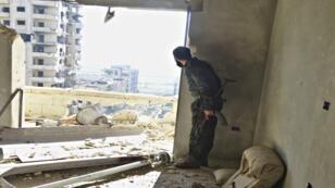 مقاتل يقف بسلاحه داخل مبنى في منطقة حمص الشمالية الغربية في الوعر في 18 يناير/كانون الثاني 2015.