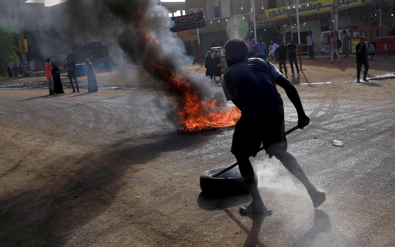 متظاهر يستخدم إطارا لسد شارع في الخرطوم عقب محاولة المجلس العسكري فض الاعتصام بالقوة ووقوع قتلى وجرحى 3 يوليو/حزيران 2019