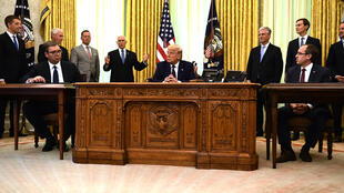 US President Donald Trump (C), Kosovar Prime Minister Avdullah Hoti (R) and Serbian President Aleksandar Vucic (L) listen to US Vice President Mike Pence during a signing ceremony, in the Oval Office of the White House in Washington, DC, on September 4, 2020