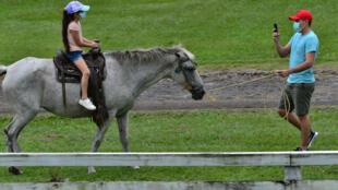 Un hombre toma una foto de una niña en un caballo a orillas del lago Yojoa, el lago natural más grande de Honduras, a unos 180 km al noroeste de Tegucigalpa, el 6 de septiembre de 2020