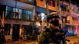 Los residentes miran a los soldados colombianos vigilando una calle durante el toque de queda impuesto en los barrios de la zona roja debido al alto número de casos de COVID-19 en Cali el 17 de julio de 2020.