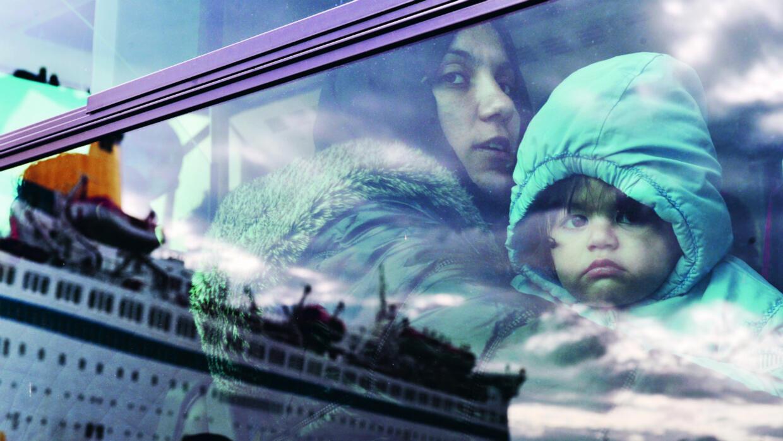 Dans le bus qui les conduit vers un centre d'hébergement, une mère et son enfant regardent le paquebot affrété par le gouvernement grec pour les transporter au Pirée en réponse à l'aggravation de la situation dans les îles grecques de Kos, Lesbos et Chios, en 2015.