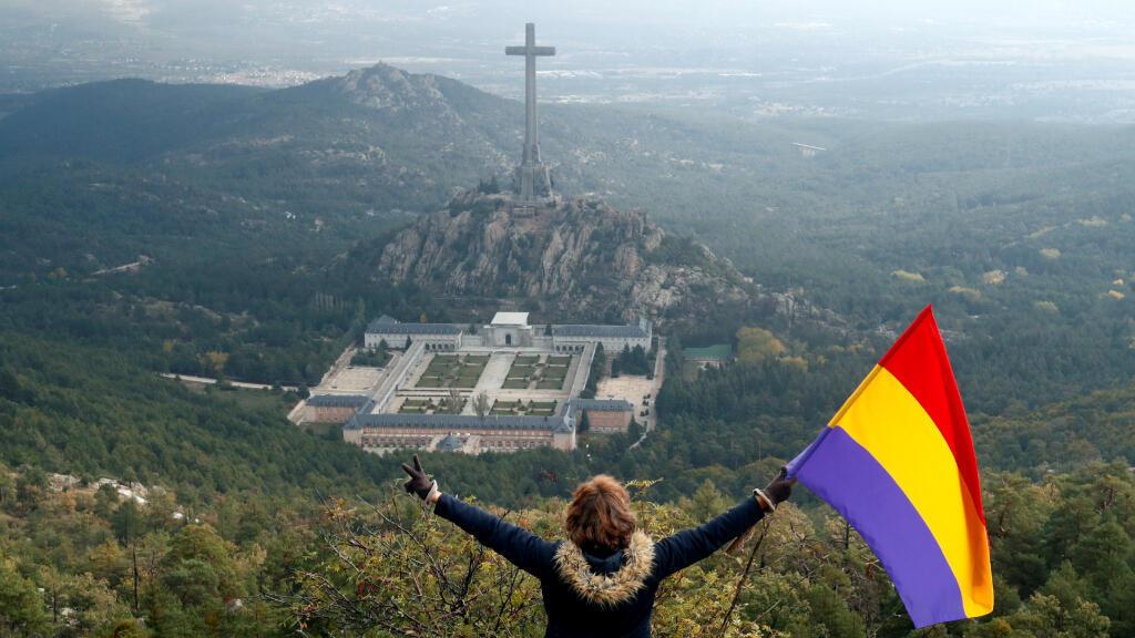 Una mujer ondea una bandera republicana, símbolo de los opositores de Francisco Franco, frente al Valle de los Caídos en Peguerinos, cerca a Madrid, España. 24 de octubre de 2019.