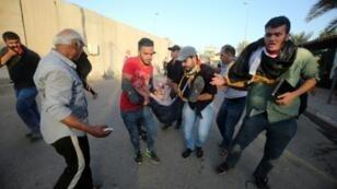 أنصار مقتدى الصدر ينقلون مصابا خلال المواجهات مع قوات الأمن في المنطقة الخضراء