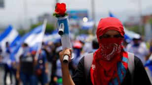 Un manifestante enmascarado sostiene un mortero casero con una flor durante la marcha para exigir la liberación de los presos políticos arrestados durante las recientes protestas contra el gobierno del presidente de Nicaragua, Daniel Ortega. Managua, Nicaragua 21 de julio de 2018