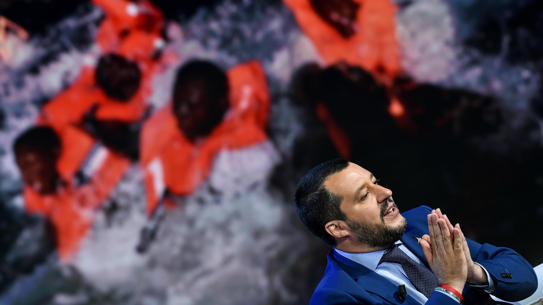 """El ministro del Interior y viceprimer ministro de Italia, Matteo Salvini, habla durante el programa de entrevistas italiano """"Porta a Porta"""", emitido por el canal italiano Rai 1, en Roma, el 20 de junio de 2018, mientras se ve una imagen con inmigrantes en el mar."""