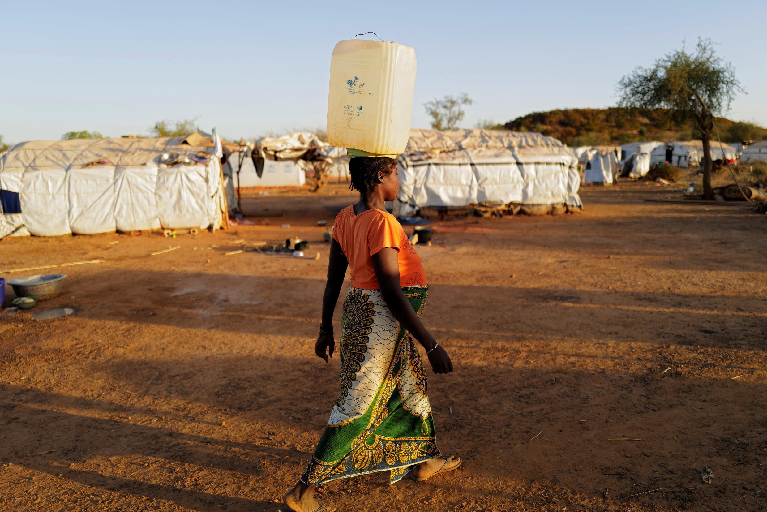 A pregnant woman carries a jerrycan of water at a camp for people displaced by conflict in Kaya, Burkina Faso.