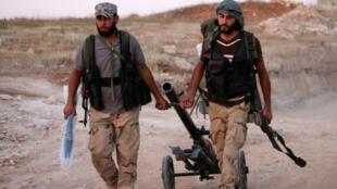 مقاتلو المعارضة السورية يسيرون بأسلحتهم بالقرب من خط المواجهة مع القوات الحكومية غرب مدينة درعا
