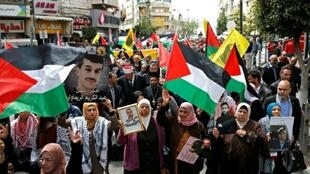 Palestinians, including Christian and Muslim clerics, march with national flags and pictures of prisoners held in Israeli jails during a rally marking Palestinian Prisoners' Day in the West Bank city of Ramallah