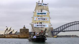Un barco exhibe pancartas contra el cambio climático mientras navega en el puerto de Sidney, Australia, el 8 de septiembre de 2018.