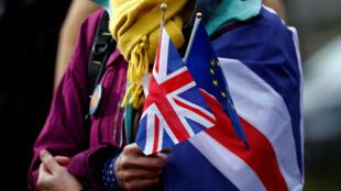 Un manifestante anti-Brexit sostiene banderas británicas y europeas durante una protesta frente al Parlamento Europeo en Bruselas, Bélgica, el 30 de enero de 2020.