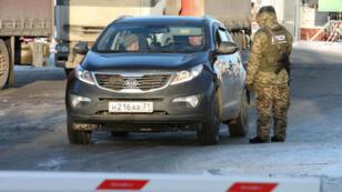 Un garde ukrainien contrôle une voiture à un poste-frontière.