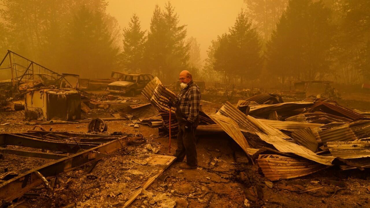 Un hombre camina por lo que queda de una casa en su propiedad destruida por un incendio forestal el sábado 12 de septiembre de 2020 en Mill City, Oregon.