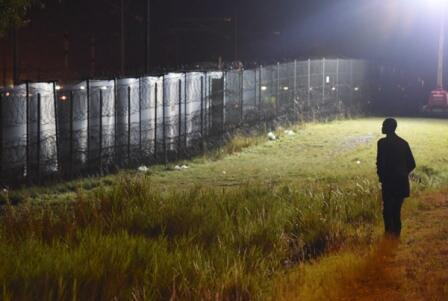 A migrant looks at the fence surrounding the Channel Tunnel near Calais. Photo: Mehdi Chebil / FRANCE 24.