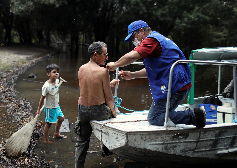 Un agente de salud vacuna a un anciano contra la gripe y el H1N1, según lo aconsejado por los funcionarios de salud para facilitar el diagnóstico de coronavirus, en medio del brote de la enfermedad del coronavirus, a lo largo de las orillas del río Negro, donde viven los Ribeirinhos (habitantes del bosque), en Manaos, Brasil, 2 de abril de 2020.