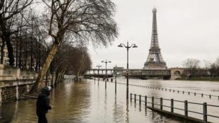 Un hombre se encuentra junto a las orillas inundadas del río Sena en París el 23 de enero de 2018 cerca de la torre Eiffel ya que el nivel del Sena ha subido a una altura de 4,57 metros.