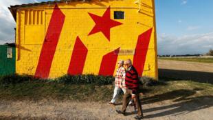 Una pareja pasea delante de un edificio con la bandera no oficial de Cataluña, en la localidad de Tona, en la provincia de Barcelona. 09/10/2017